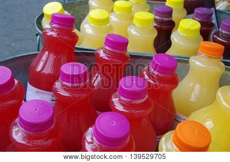 Ice cold colorful drinks  on ice in steel tubs outdoors