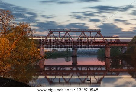 Railway bridge over the river at sunset with blurred light on a passing train