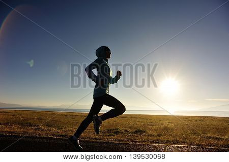 healthy young fitness woman runner running on sunrise seaside trail
