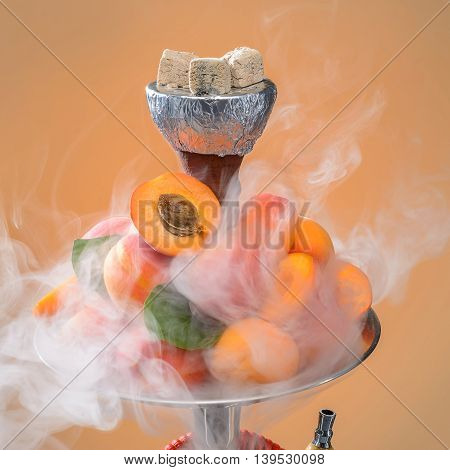 Smoking hookah with apricot fruits on its tray