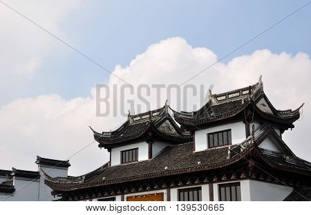Chinese architecture on a building in front of white clouds in Fengjing Town Shanghai China.
