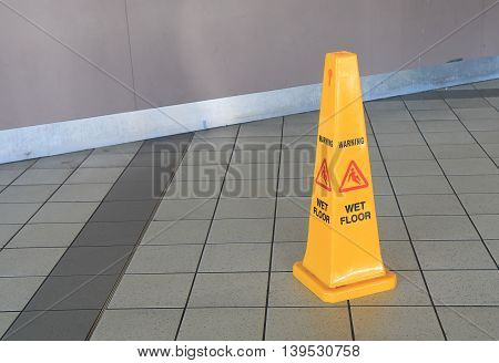 Wet floor warning sign on tiled floor