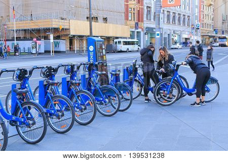 MELBOURNE AUSTRALIA - JULY 16, 2016: Unidentified people hire bicycles in Melbourne downtown. The bicycle hire scheme is designed for short trips across the city and to ease traffic congestions.