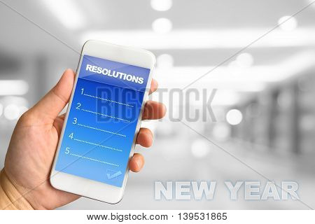Woman hand holding smartphone against white grey bokeh abstract background Resolutions concept