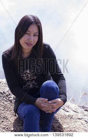 Thai woman with backpack sitting on cliff , people