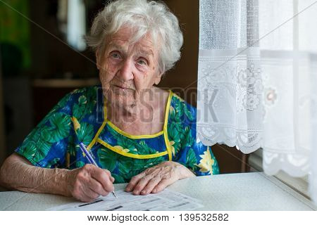 An elderly woman writes the bills for communal services.