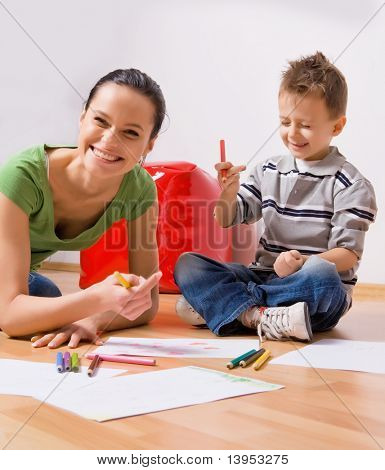 mother and a 5-year old son painting on paper
