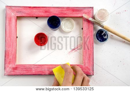 Craft wood picture frame with woman hands paints sponge and paintbrush
