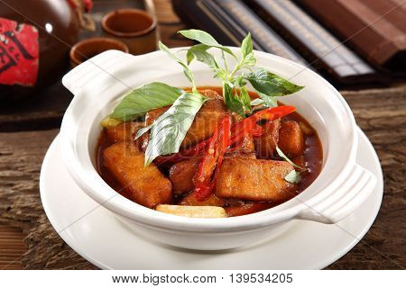 Braised tofu with herbs in white bowl on the table