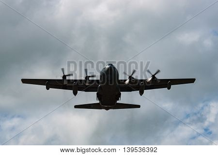 Four engined silhouetted cargo aircraft flying overhead