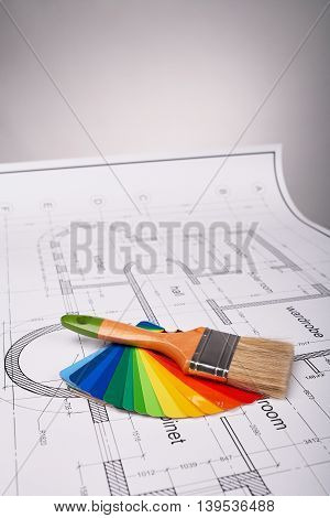 Construction of the building layout, paint brush, building drawing on paper, paint brush and color samples, selecting paint colors, construction planning