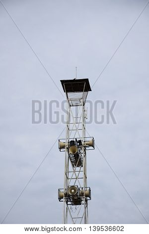 A Loudspeakers broadcast tower on sky background.