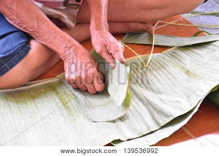 Hand of thai old woman posing tear the banana leaf, artificial