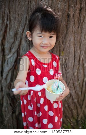 Asian Girl Eating Ice Cream In The Summer Day. Outdoors.