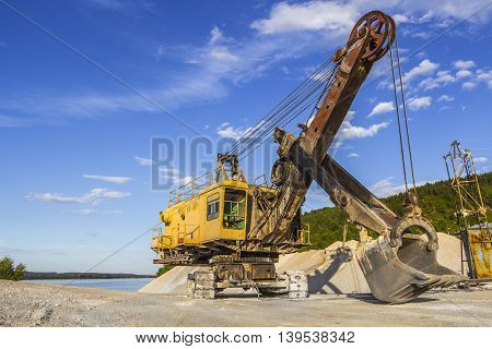 Old yellow excavator on the background of blue sky