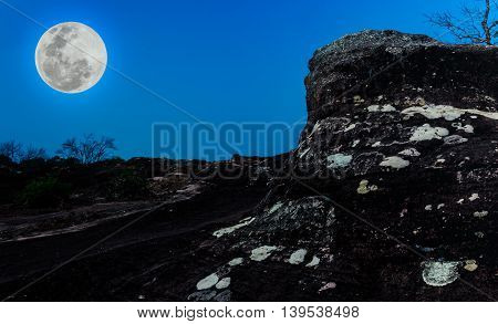 Silhouettes Of Boulders Against Blue Sky And Beautiful Full Moon At Night. Outdoors.