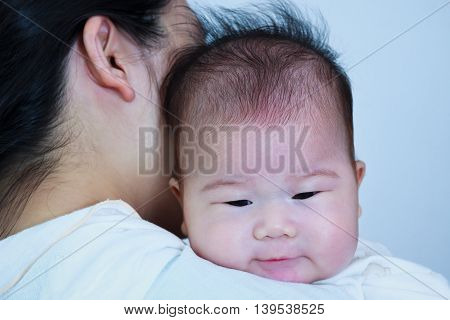 Mother and baby Lovely asian girl resting on her mother's shoulder. Happy family spending time togetherness. Mother's Day celebration.