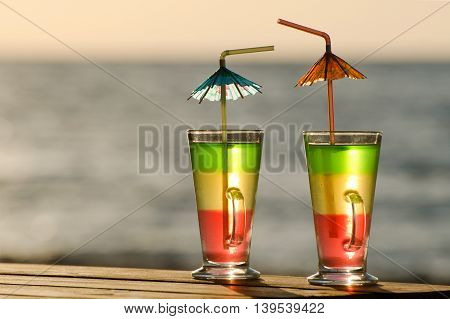 Two colorful cocktails in the morning sun on the sea background close-up empty space