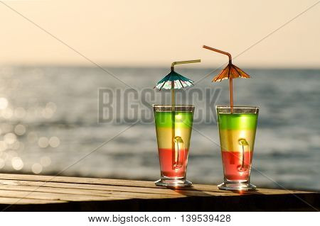 Two colored cocktail on a wooden table on the beach in the morning sun the empty space