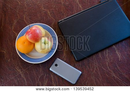 Top view of a laptop a fruit plate and a smartphone. Break for lunch