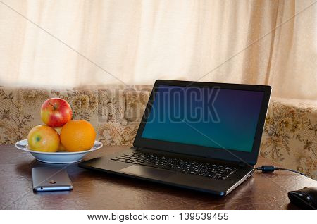 Laptop on a table in a cozy kitchen with a plate of fruit a smartphone. Break