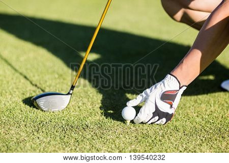 Cropped image of golfer placing golf ball on tee at field