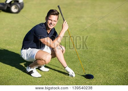 Portrait of happy man placing golf ball on tee while crouching on field