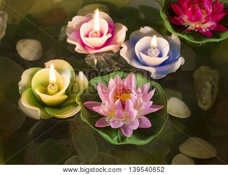 Group of colorful lotuses and candles in the water, meditation and relax