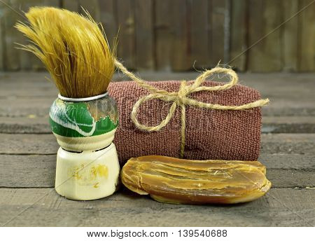 Vintage shaving still life with old shaving brush, brown towel and hand made soap bar