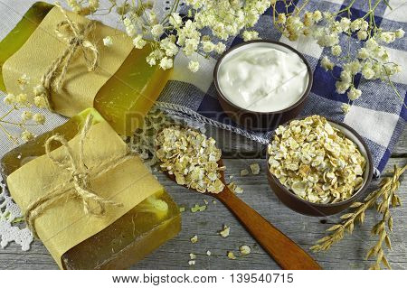 Handmade soap with oats, milk cream and flowers on the table background