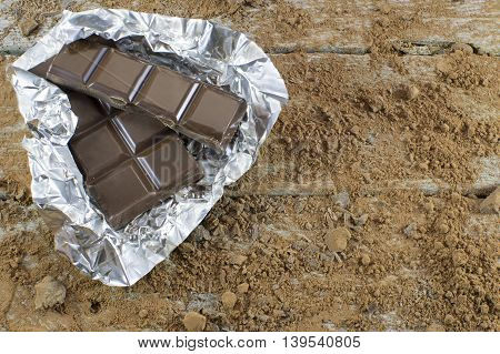 Chocolate pieces in foil wrapper on cocoa powder background