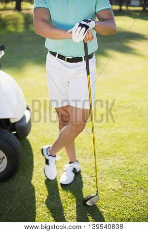 Low section of golfer with golf club standing on field