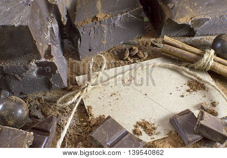 Dark chocolate still life with greeting card and candies