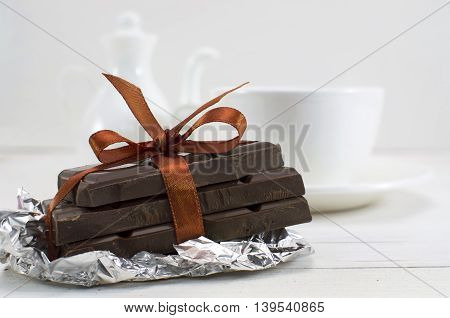 Still life with chocolate pieces with orange bow and defocused porcelain tea set