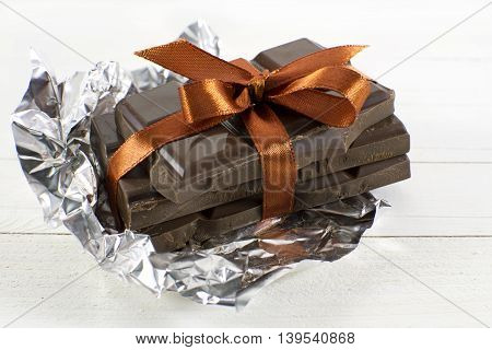Pile of chocolate pieces with orange bow on white