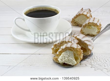 Porcelain coffee cup with fancy cake on white