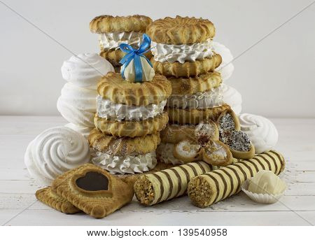 Heap of fancy cakes with cookies, marshmallows and white chocolate candy on top