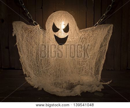 Scary handmade ghots hanging on chain in candle light, Halloween concept