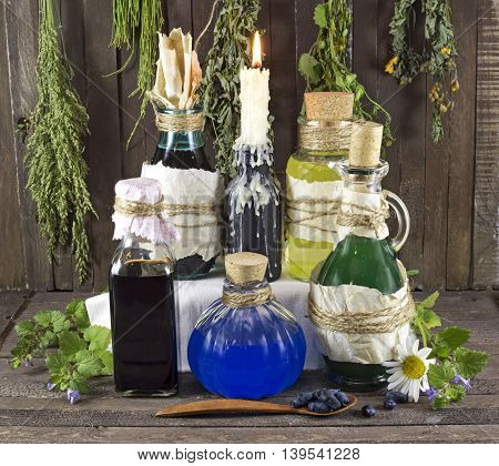 Alternative medicine concept with old bottles, healing herbs and berries