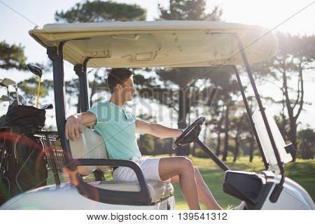 Side view of smart man sitting in golf buggy on field