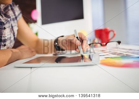 Woman using digital tablet on table at creative office
