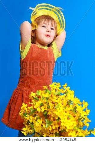 Little girl with flowers on blue background