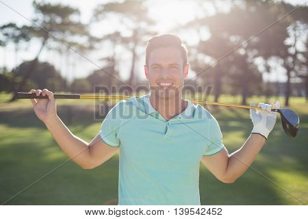 Portrait of smart man carrying golf club while standing on field