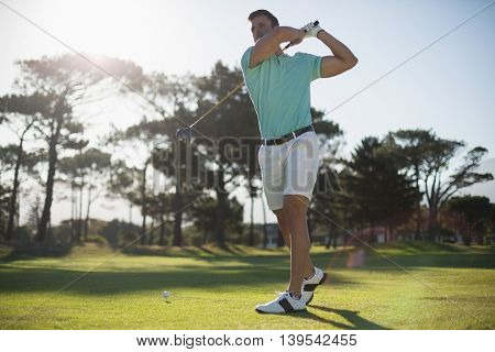 Full length of handsome golfer man taking shot while standing on field