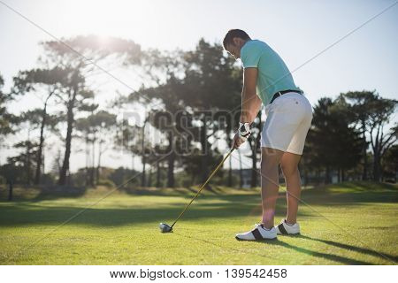Full length of young man playing golf while standing on field