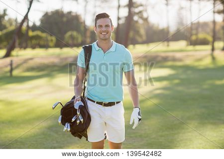 Portrait of smiling young man carrying golf bag while standing on field
