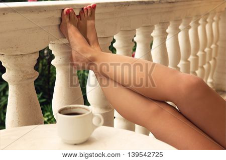 Woman`s legs with magenta nail polish on balcony fence and coffee cup on table.