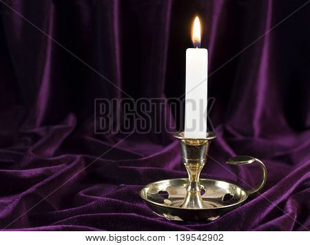 One burning candle on purple velvet background