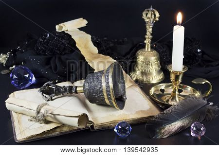 Magic still life with bells, open book, old scroll and candle