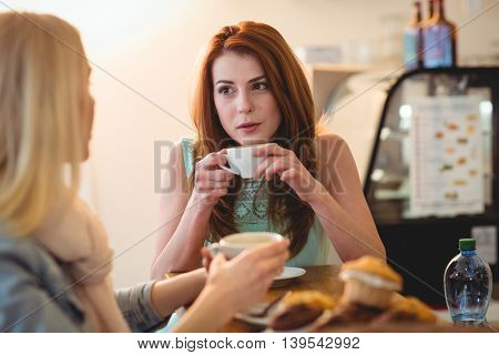 Attractive woman talking to female friend at cafe
